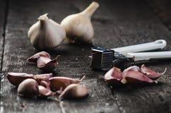 Cravos-da-índia de alho em uma tabela preta de madeira Bulbo fresco do alho com a imprensa de alho do ferro Fundo do vintage Faze Foto de Stock