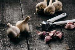 Cravos-da-índia de alho em uma tabela preta de madeira Bulbo fresco do alho com a imprensa de alho do ferro Fundo do vintage Faze Fotografia de Stock Royalty Free