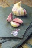 Cravos-da-índia de alho na pedra azul Fotografia de Stock Royalty Free
