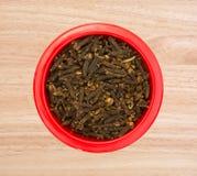 Cravos-da-índia inteiros em um prato vermelho na vista superior contrária Imagem de Stock