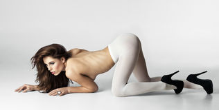 The Crawl. Full length studio photo of beautiful, sexy brunette woman on hands and knees, on white background Stock Photo