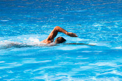 Crawl style swim. Young man swim crawl style in outdoor swimming pool, sunny summer day royalty free stock photos
