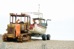 Crawler with boat on tow. Yellow tracked vehicle towing a crabbing boat on a trailer on the shingle beach at Weybourne Norfolk UK Stock Images