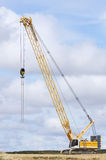 Crawler crane. View of a yellow crane in a landscape of white clouds Stock Photos