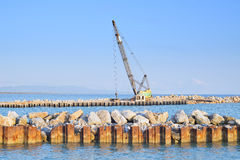 Crawler Crane at work on a river and sea shore Stock Photography