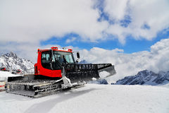 Crawler loader on a mountain top. A driver driving a crawler loader to work on a snow field, Zugspitze Stock Photo