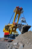 Crawler-mounted excavator. Extract  iron ore in opencast mine on bleu sky background Stock Photo