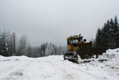 Crawler tractor bulldozer mountain landscape. Crawler tractor bulldozer - stands on a lawn of a mountain forest after clearing the road from snow. The photo has Stock Image