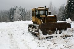Crawler tractor bulldozer mountain landscape. Crawler tractor bulldozer - stands on a lawn of a mountain forest after clearing the road from snow. The photo has Stock Photography