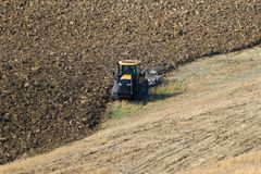 A crawler tractor is working on plowing a field on a September day, Italy Stock Images