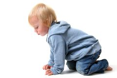 Crawling. Child or toddler practising to crawl. young blond boy in jeans crawling on all four isolated on white Stock Images