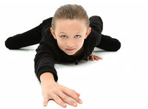 Crawling 7 year old Girl in Black. Adorable 7 year old girl in black suit crawling on white floor stock image