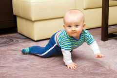 Crawling on all fours. Happy boy crawling on all fours at home Stock Photo