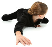 Crawling Away 7 Year Girl. Adorable 7 year old girl in black suit crawling and looking behind on white floor royalty free stock photography