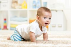 Crawling baby boy indoors. Crawling funny baby boy indoors at home Royalty Free Stock Images
