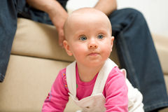 Crawling baby girl. Her father sits on the back and watching Stock Photo