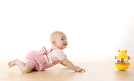 Crawling baby girl. Baby girl crawling towards a toy on the floor royalty free stock images