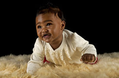 Crawling baby girl. A beautiful multi racial nine month old baby girl crawls her way across the deep white fur rug she is on Royalty Free Stock Photo