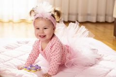Crawling baby girl. Beautiful little baby girl wearing pink tutu skirt, crawling on the floor, making her first independent moves royalty free stock images