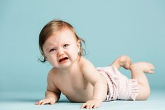 Crawling baby girl crying on the floor. Baby blue background. Sad kid Royalty Free Stock Images