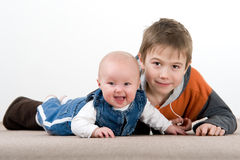 Crawling baby girl and her brother Stock Photo