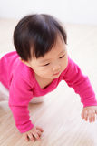 Crawling baby girl on living room floor Royalty Free Stock Photography