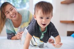 Crawling baby. Happy mother looking at her crawling baby stock image