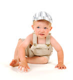 Crawling boy. Sitting boy with a cap Royalty Free Stock Image