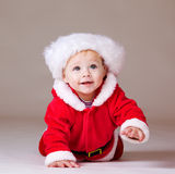 Crawling Christmas baby. Over grey Stock Photos