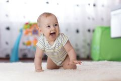 Crawling funny baby boy indoors at home royalty free stock photography