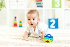 Crawling funny baby boy at nursery royalty free stock photo