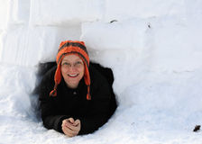 Crawling through Igloo Doorway. A bundled up woman crawls out of a homemade igloo Stock Photo