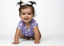 Happy, crawling baby in purple onesie stock photography