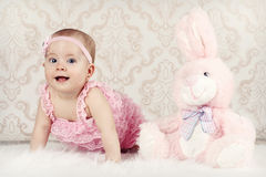 Crawling little baby girl with plush rabbit Royalty Free Stock Photos