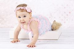 Crawling little baby girl. Studio portrait of adorable toddler stock photos