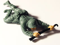 Crawling toy soldier. Green plastic toy soldier crawling on white background royalty free stock photos