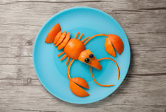 Crayfish made of orange. On plate and board stock images