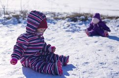 Craying two children in a white snow in the warm suit siting in the snow royalty free stock photo