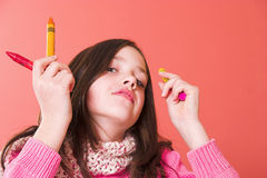 Crayon advertisment. Girl holding a few crayons Royalty Free Stock Image