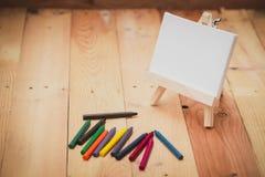 Crayon avec la toile de peinture sur le fond en bois Photographie stock libre de droits