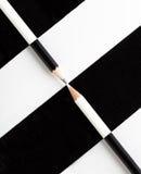 Crayon blanc et crayon noir placé sur la couleur opposée Photos stock