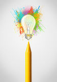 Crayon close-up with colored paint splashes and lightbulb Royalty Free Stock Photo