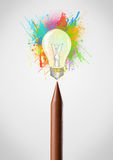 Crayon close-up with colored paint splashes and lightbulb Royalty Free Stock Photos