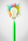 Crayon close-up with colored paint splashes and lightbulb Royalty Free Stock Image