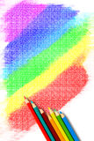 Crayon Colors and Rainbow. Top view of crayon colors arranged on a white paper filled with rainbow freehand drawing royalty free stock image