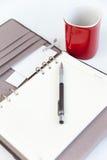 Crayon d'agenda de page blanc et cuvette de café rouge Photographie stock libre de droits