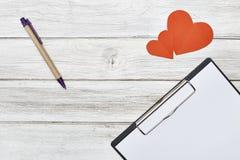 Crayon de bloc-notes et papier rouge de deux coeurs Photos libres de droits