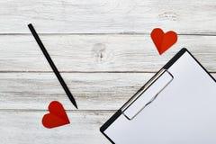 Crayon de bloc-notes et papier rouge de deux coeurs Image stock