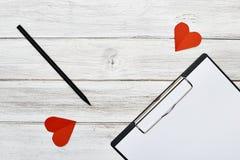 Crayon de bloc-notes et papier rouge de deux coeurs Photos stock