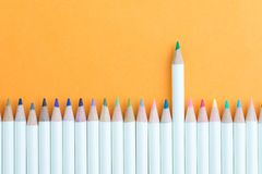 Crayon de couleur dans la rangée avec de support le vert un employant en tant que créativité unique et individuelle, idée de dire photographie stock libre de droits